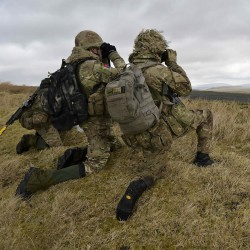 Soldiers from the Royal Artillery act as Forward Controllers, directing the artillery fire from the vantage of a ridge-line viewpoint during Exercise Steel Sabre.